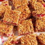 Strawberry Rhubarb Crumble Bars on parchment and white marble sliced over head
