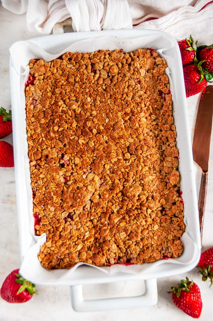 Strawberry Rhubarb Crumble Bars unsliced in white baking dish with copper knife over head
