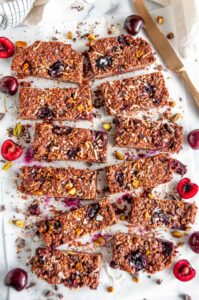 Chocolate Cherry Coconut Granola Bars on parchment with gold knife over head