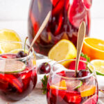 Fruity Red Wine Sangria with citrus fruits and cherries in pitcher and stemless wine glasses with gold spoons