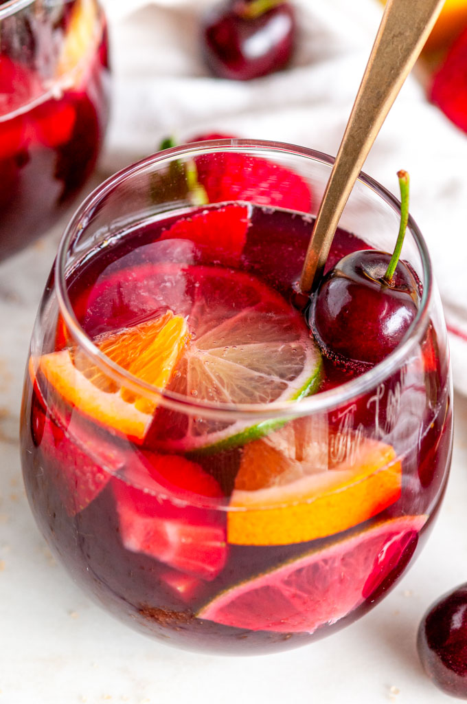Fruity Red Wine Sangria with citrus fruits and cherries in stemless wine glass with gold spoon close up