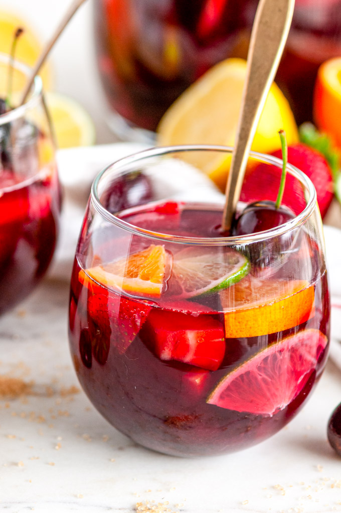 Fruity Red Wine Sangria with citrus fruits and cherries in stemless wine glass with gold spoon side view close up