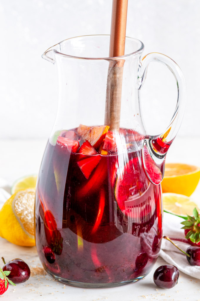 Fruity Red Wine Sangria with citrus fruits and cherries in pitcher with wood spoon side view