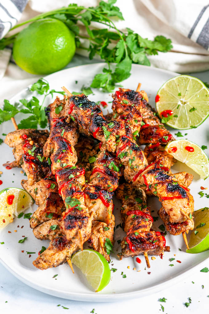 Grilled Lime Chicken Skewers with lime slices, cilantro, and a Sriracha drizzle on a gray plate angled over head view