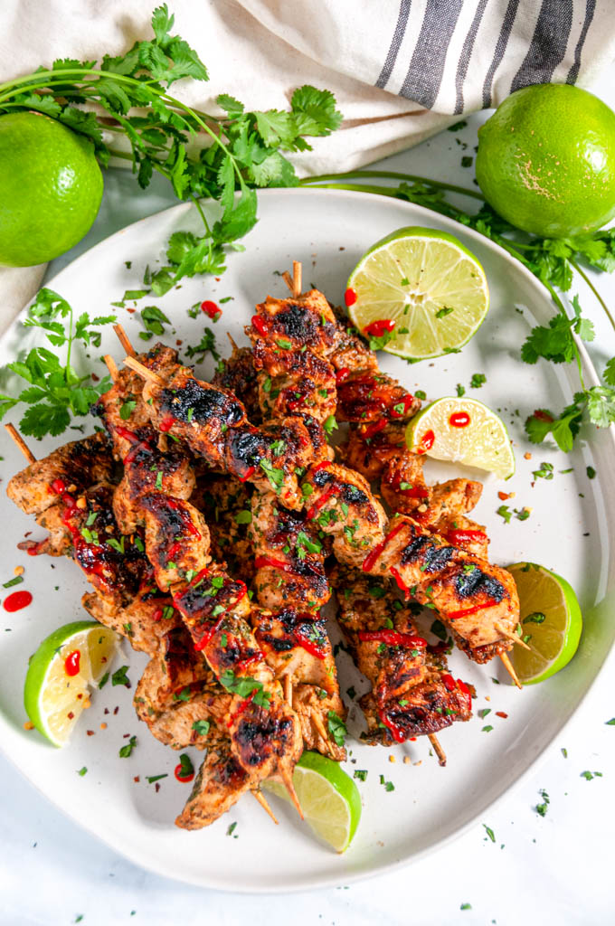 Grilled Lime Chicken Skewers with lime slices, cilantro, and a Sriracha drizzle on a gray plate over head view