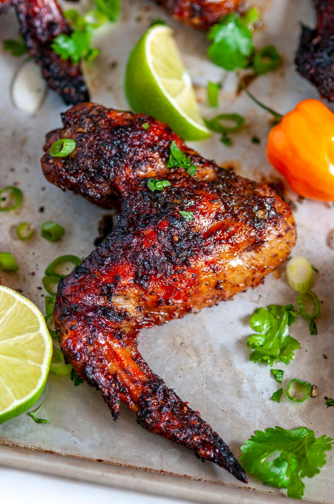Jamaican Jerk Chicken Wings (Air Fryer + Oven Baked Methods) on sheet pan with limes and habanero pepper close up side view