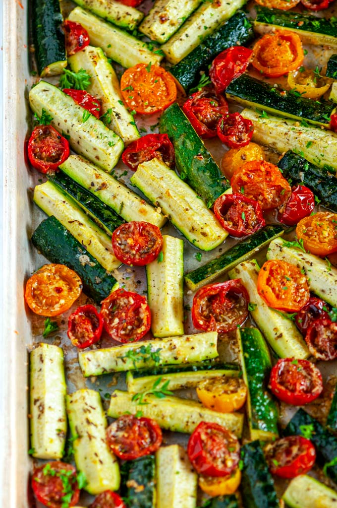 Roasted Parmesan Zucchini and Tomatoes on a gray rimmed baking sheet over head view close up
