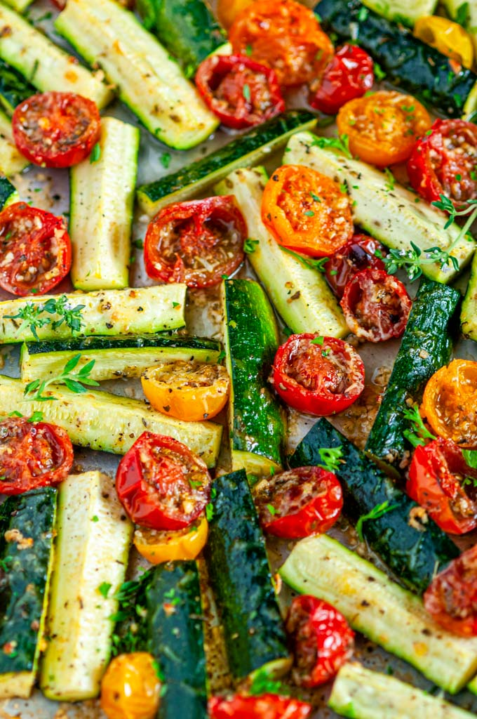 Roasted Parmesan Zucchini and Tomatoes on a gray rimmed baking sheet close up