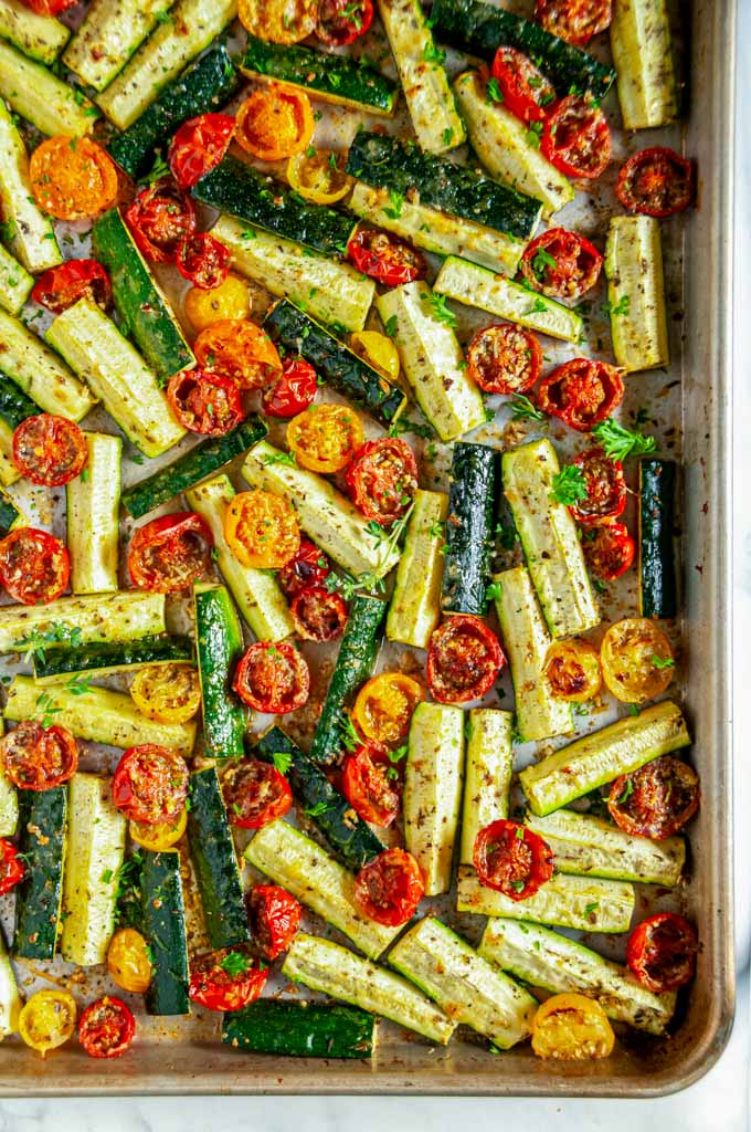 Roasted Parmesan Zucchini and Tomatoes on a gray rimmed baking sheet over head view