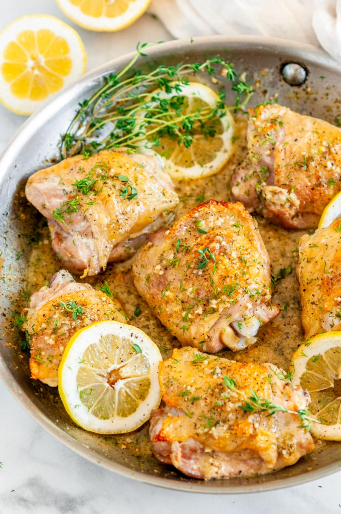 Skillet Lemon Dill Chicken Thighs in all clad pan with tea towel on white marble over head view close up