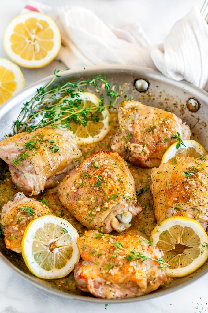 Skillet Lemon Dill Chicken Thighs in all clad pan with tea towel on white marble over head view