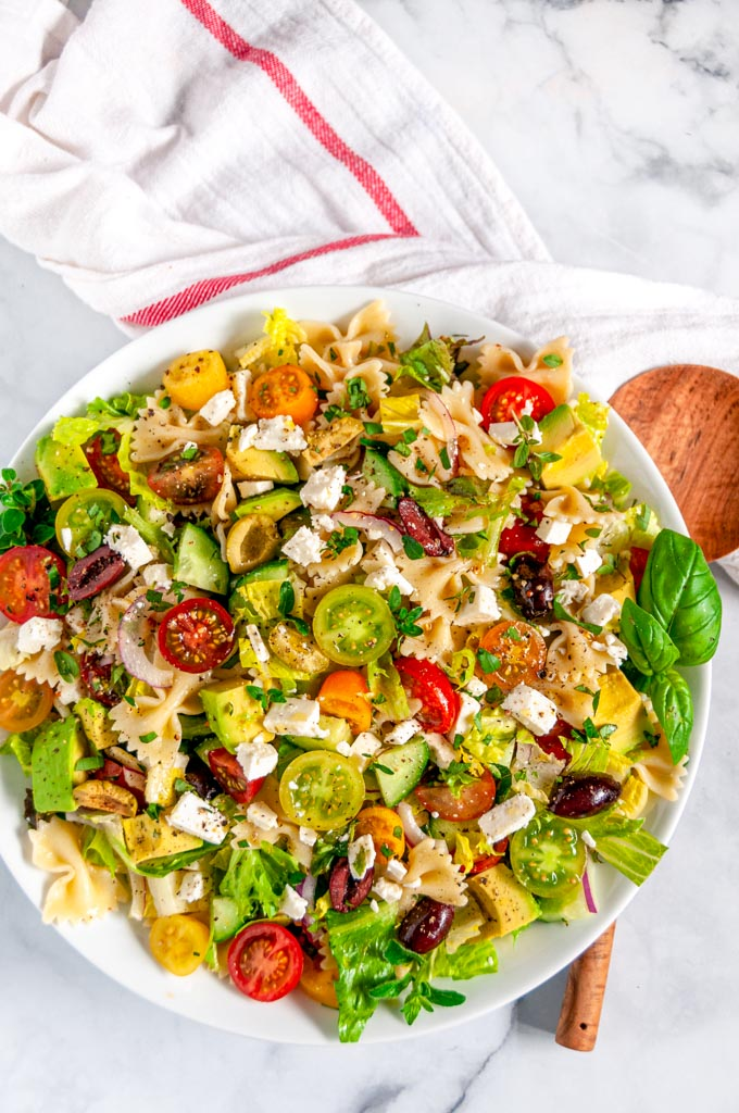 Summertime Greek Pasta Salad in white bowl with wood spoon overhead view