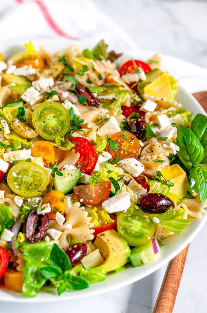 Summertime Greek Pasta Salad in white bowl side with wood spoon view close up