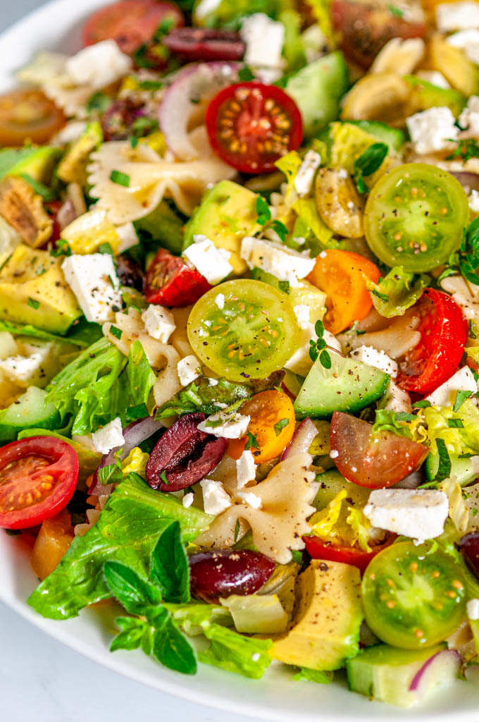 Summertime Greek Pasta Salad in white bowl side view close up