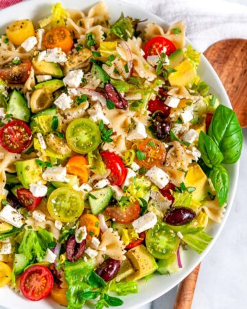 Summertime Greek Pasta Salad in white bowl with wood spoon overhead view close up