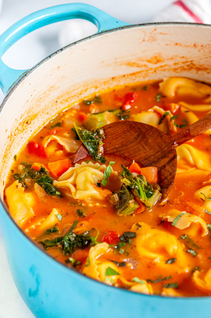 Vegetable Tortellini Soup in blue le creuset pot with wood spoon on white marble side close up view