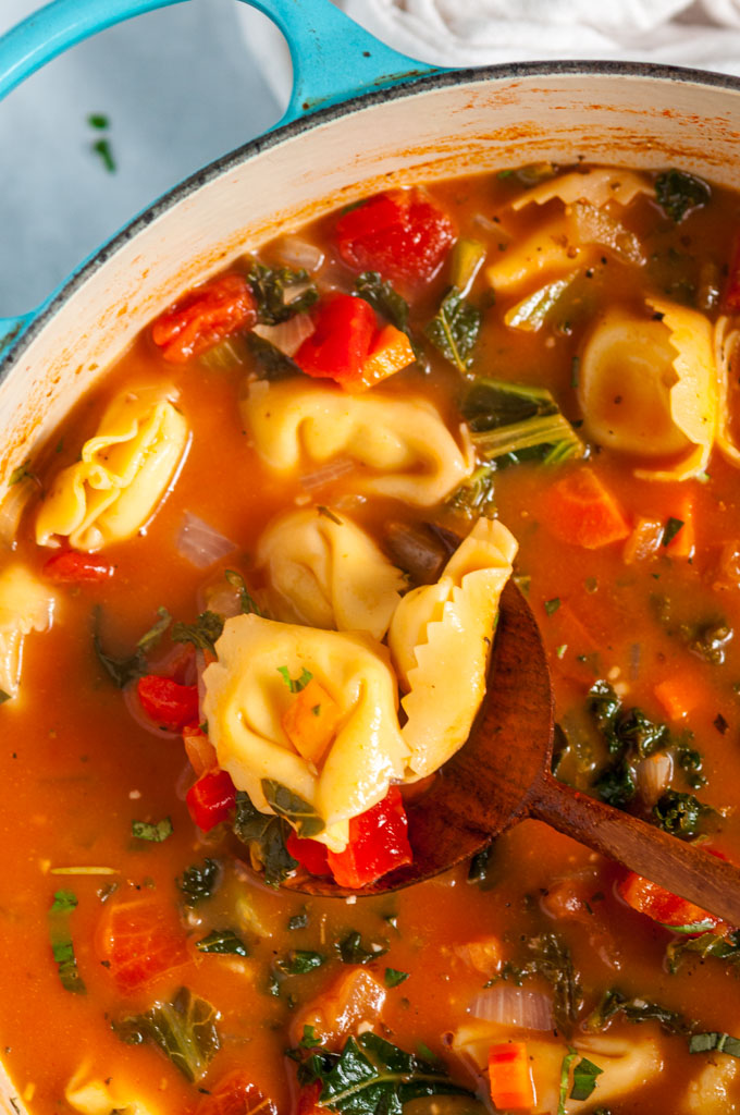 Vegetable Tortellini Soup in blue le creuset pot with wood spoon on white marble overhead close up view