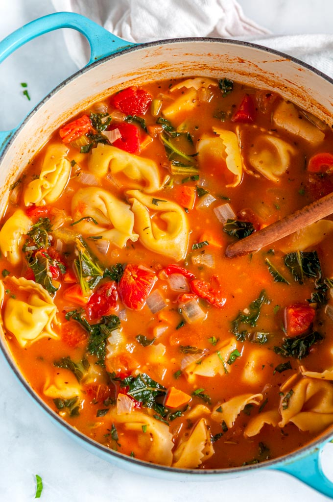 Vegetable Tortellini Soup in blue le creuset pot with wood spoon and white tea towel on white marble overhead view