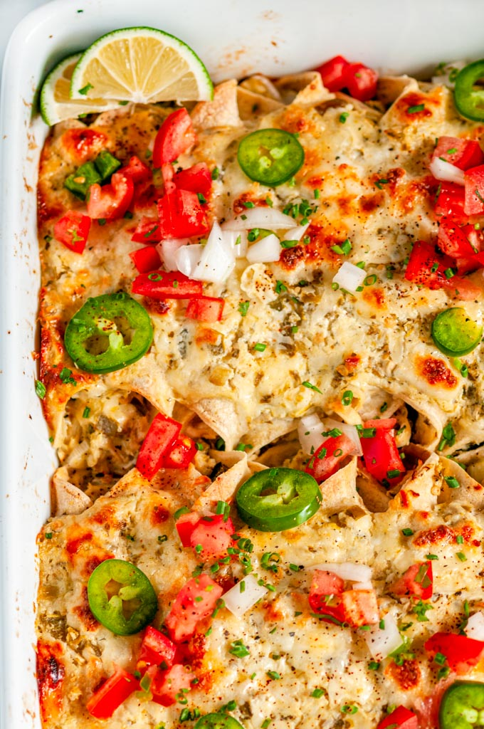 Chicken Enchiladas Suizas in white casseroled dish on marble over head close up