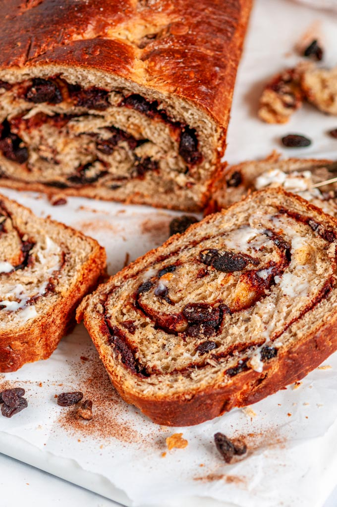 Cinnamon Raisin Swirl Bread sliced with butter on white marble close up