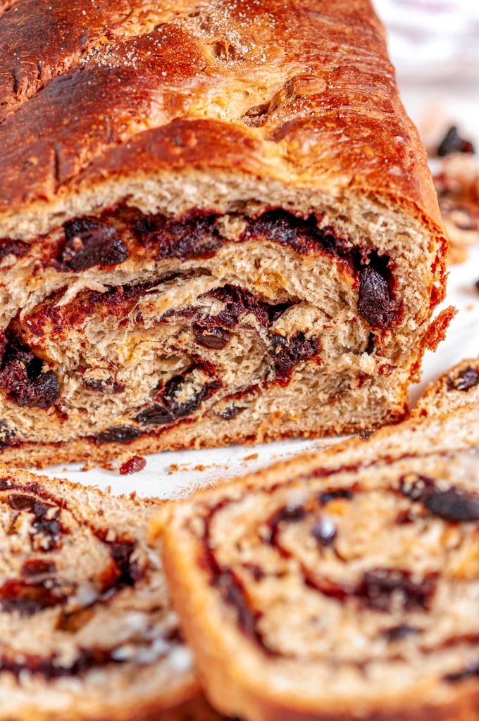 Cinnamon Raisin Swirl Bread sliced with butter on white marble side view close up