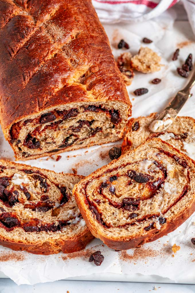 Cinnamon Raisin Swirl Bread sliced with butter and gold knife on white marble