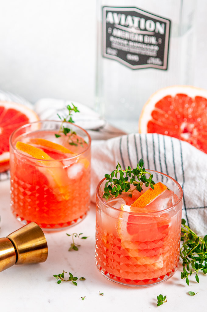 Grapefruit Thyme Gin and Tonic with Aviation Gin bottle on white marble side view