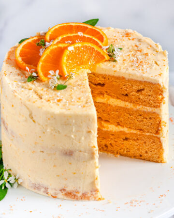 Orange Cake with Zesty Cream Cheese Frosting with orange slices and sage leaves on white cake stand slice removed side view