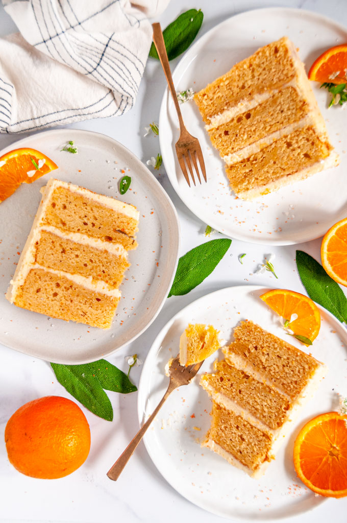 Orange Cake with Zesty Cream Cheese Frosting three slices on white plates with gold forks, orange slices, and sage leaves over head