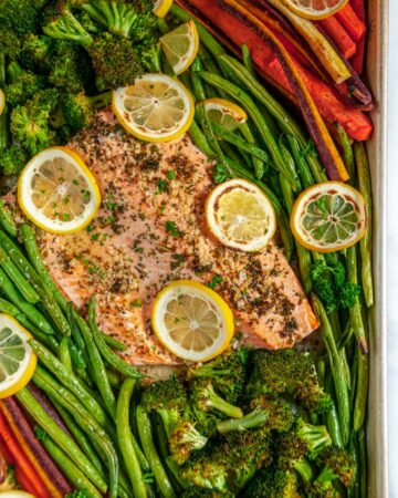 Sheet Pan Lemon Herb Salmon and Veggies with green beans, carrots, broccoli, and lemon slices over head