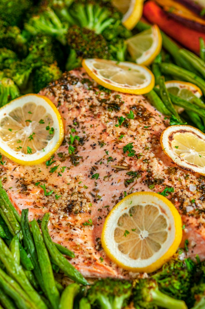 Sheet Pan Lemon Herb Salmon and Veggies with green beans, carrots, broccoli, and lemon slices close up