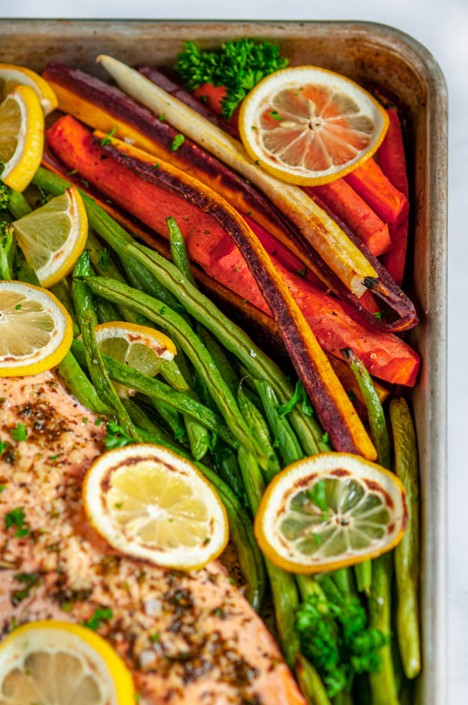 Sheet Pan Lemon Herb Salmon and Veggies with green beans, carrots, broccoli, and lemon slices corner close up