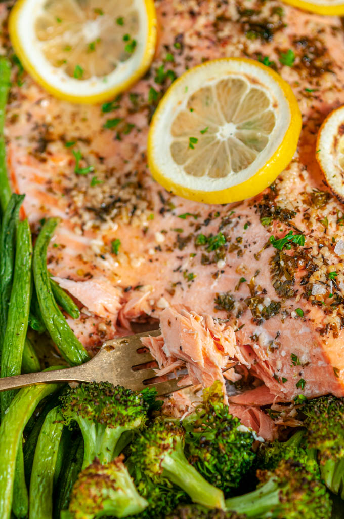 Sheet Pan Lemon Herb Salmon and Veggies with green beans, carrots, broccoli, lemon slices and gold fork close up