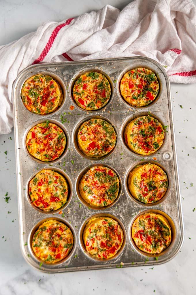 Spinach Tomato Mini Frittatas in metal muffin tin over head
