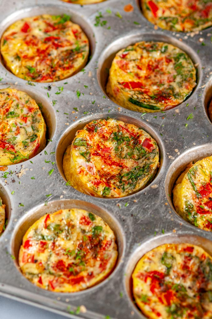 Spinach Tomato Mini Frittatas in metal muffin tin side view close up