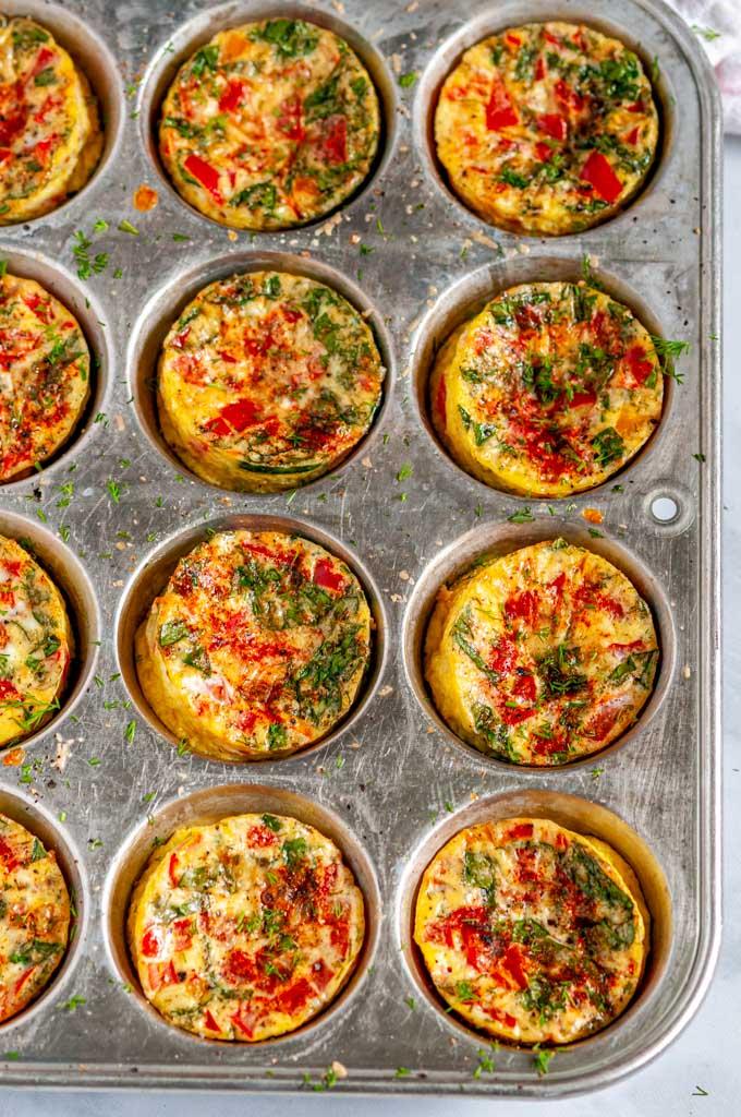 Spinach Tomato Mini Frittatas in metal muffin tin overhead