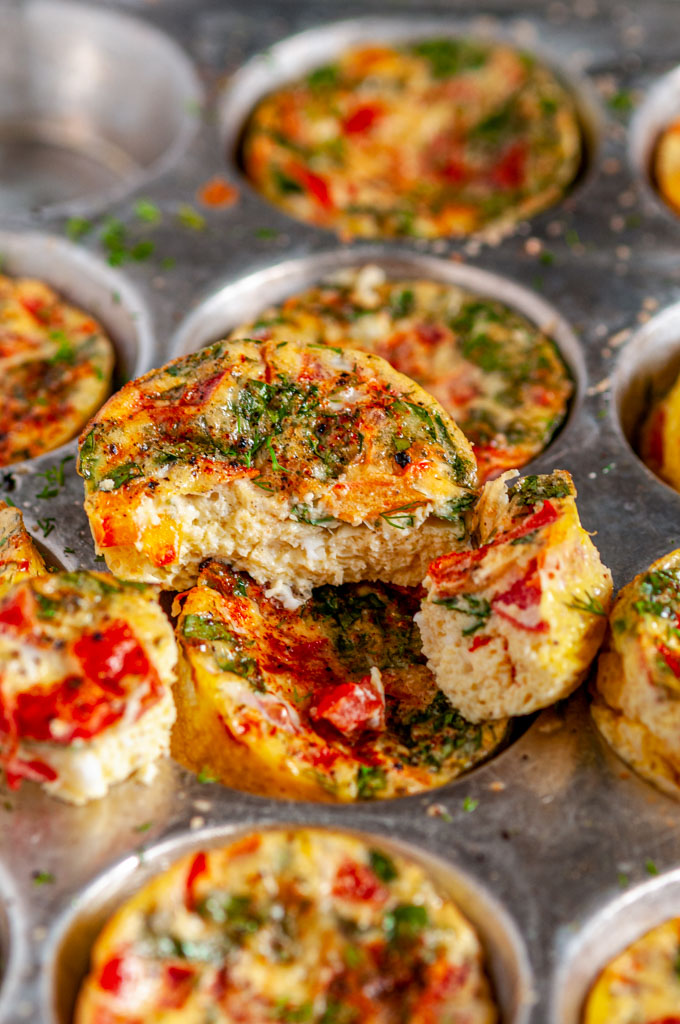 Spinach Tomato Mini Frittatas in metal muffin tin sliced close up