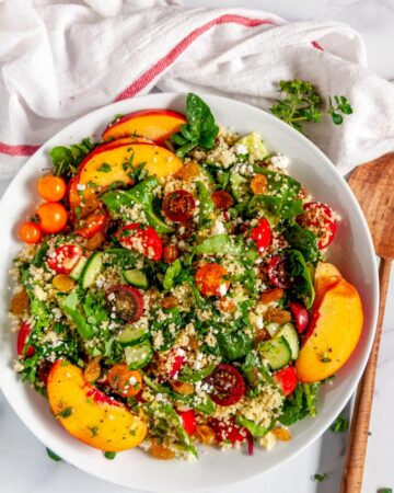 Summer Harvest Couscous Salad in white bowl on marble with wood spoon and tea towel over head view