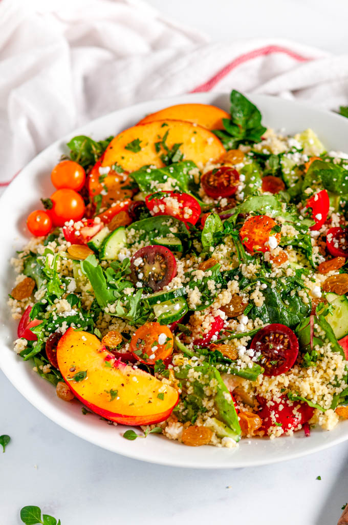 Summer Harvest Couscous Salad in white bowl with tea towel close up side view