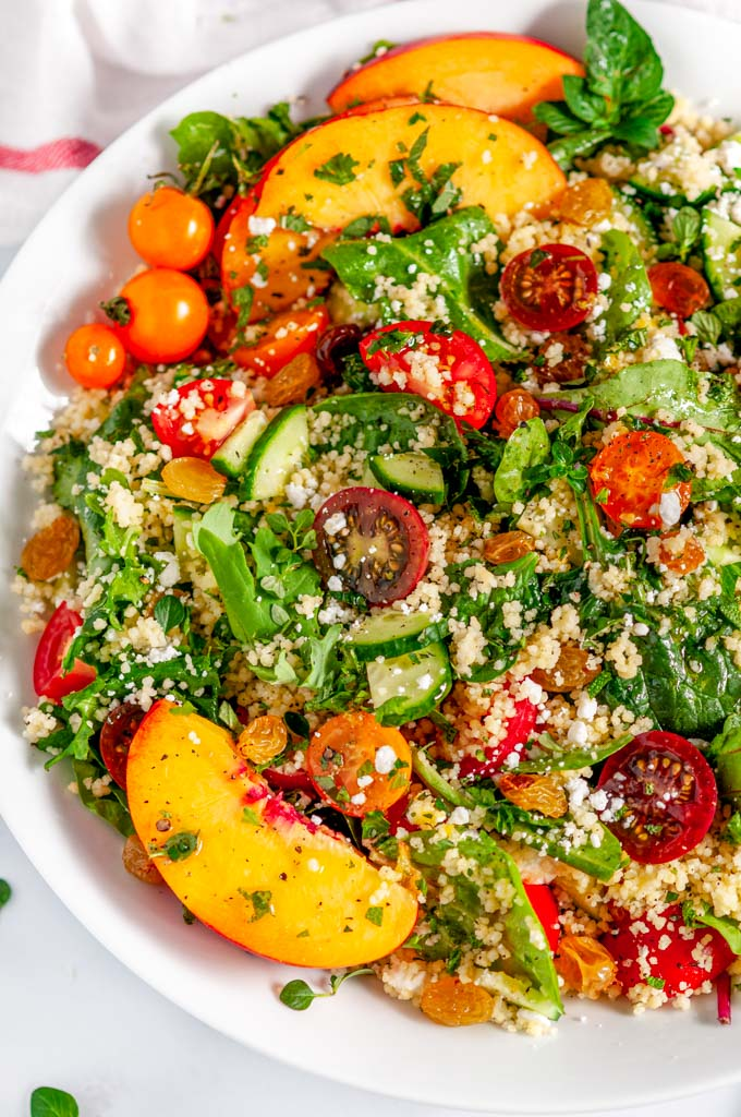 Summer Harvest Couscous Salad in white bowl with tea towel close up over head view