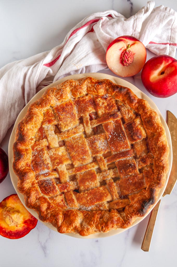 Summer Peach Pie in red pie pan on white marble over head view