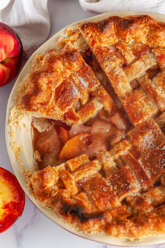 Summer Peach Pie in red pie pan on white marble slice removed over head view