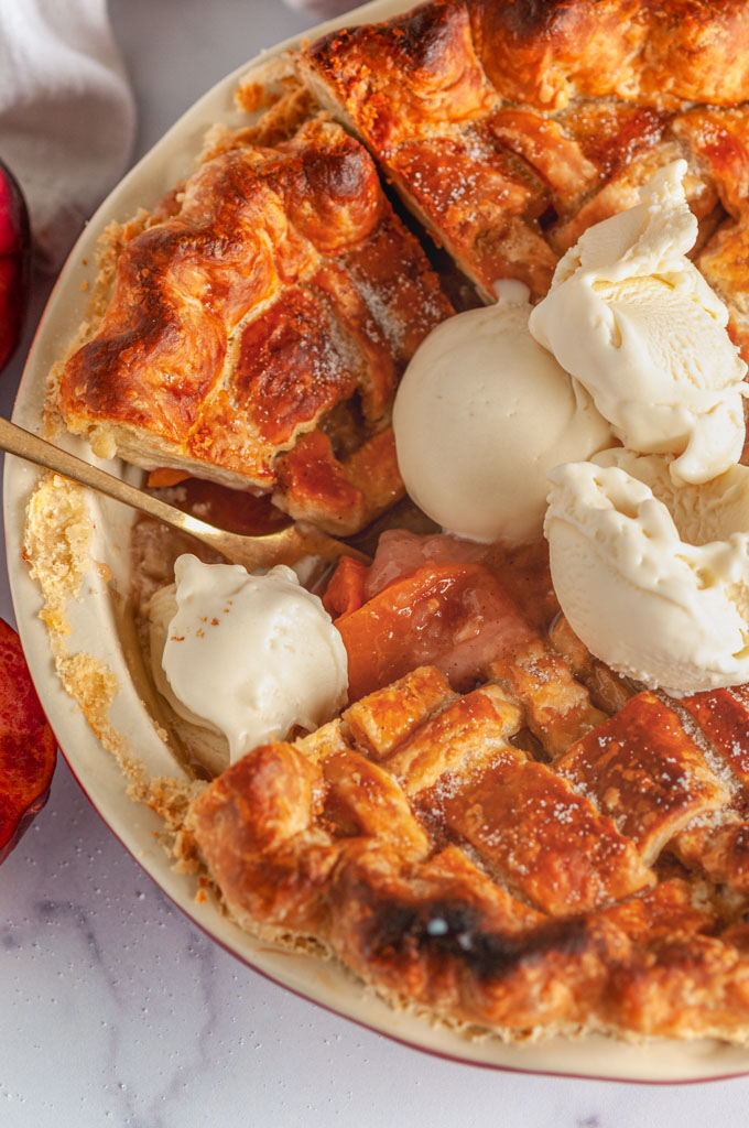 Summer Peach Pie in red pie pan on white marble with French vanilla ice cream and gold fork close up over head