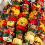 Balsamic Chicken Vegetable Kabobs on white platter overhead view close up