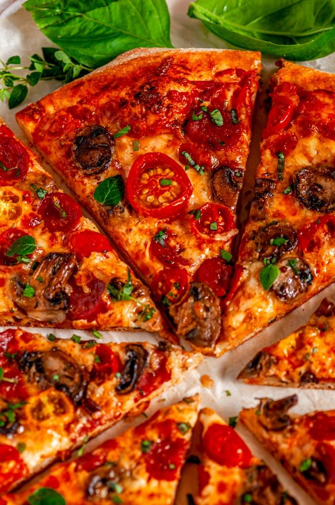 Cheesy Pepperoni Mushroom Pizza sliced over head close up