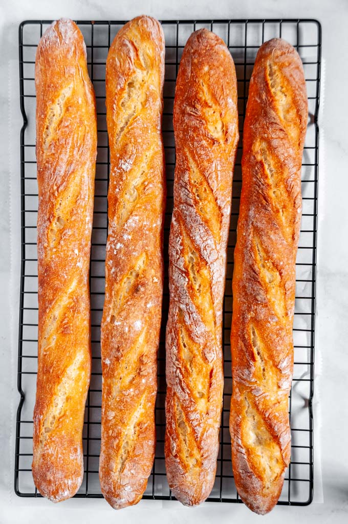 Classic crusty French baguettes baked on black wire rack and white marble over head view