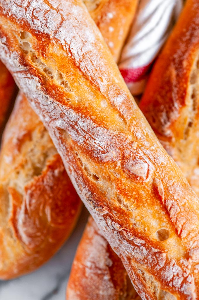 Classic crusty French baguettes with tea towel on white marble close up view
