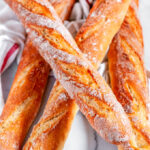 Classic crusty French baguettes with tea towel on white marble over head view