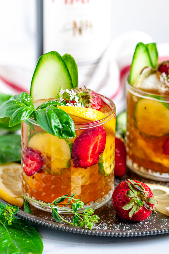 Classic Pimm's Cup Cocktail with lemon, cucumber, and strawberry slices garnished with basil leaves in glasses side view