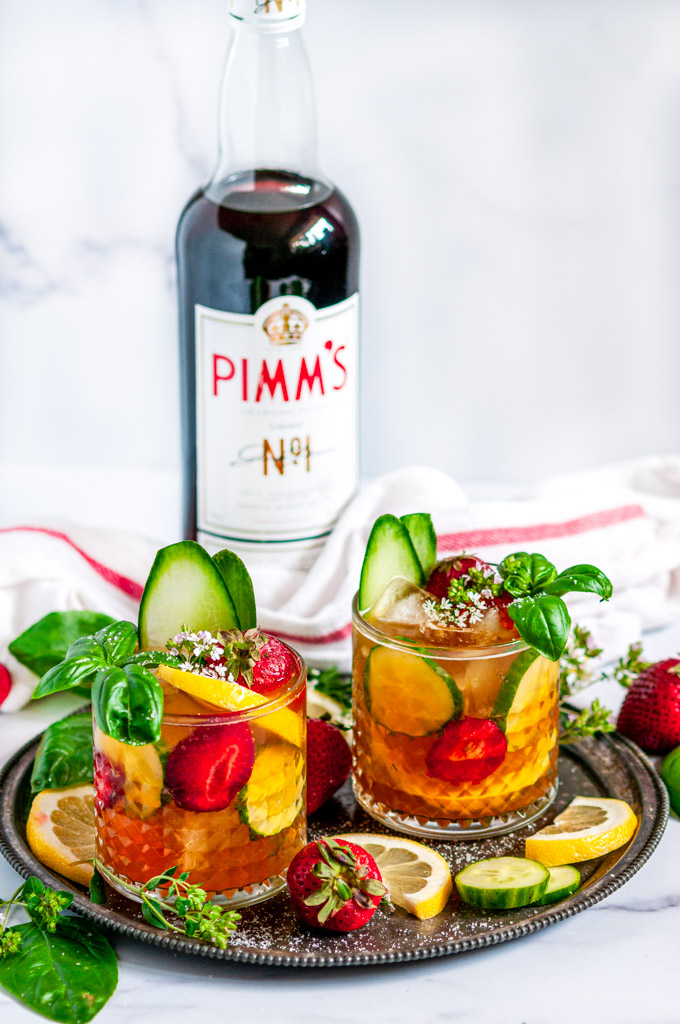 Classic Pimm's Cup Cocktail with lemon, cucumber, and strawberry slices garnished with basil leaves in glasses full view